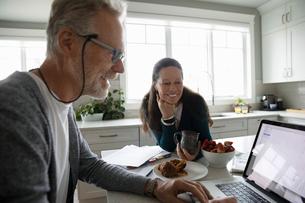 Senior couple using laptop in kitchenの写真素材 [FYI02334760]