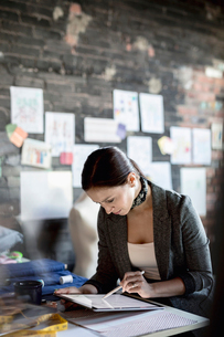 Focused female fashion designer using digital tablet in officeの写真素材 [FYI02334811]