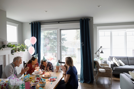 Multi-generation family celebrating toddler daughter s birthday at dining tableの写真素材 [FYI02334814]