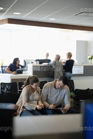 Pregnant couple filling out insurance paperwork in clinic waiting roomの写真素材 [FYI02334827]