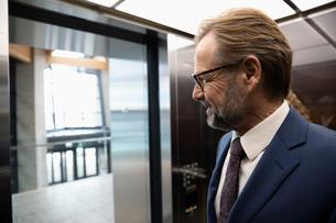 Smiling businessman in elevatorの写真素材 [FYI02334846]