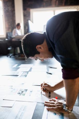 Creative businessman editing proofs on office floorの写真素材 [FYI02334852]