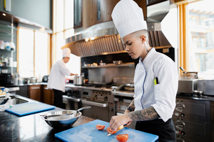 Female prep cook slicing tomatoes in restaurant kitchenの写真素材 [FYI02334867]