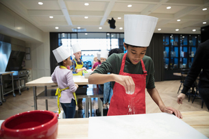 Boy sprinkling flour on surface in cooking classの写真素材 [FYI02334871]