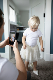 Father with camera phone photographing cute toddler daughter in high heelsの写真素材 [FYI02334874]