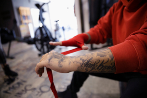 Close up tough female boxer with tattoos wrapping wrists in gymの写真素材 [FYI02334902]