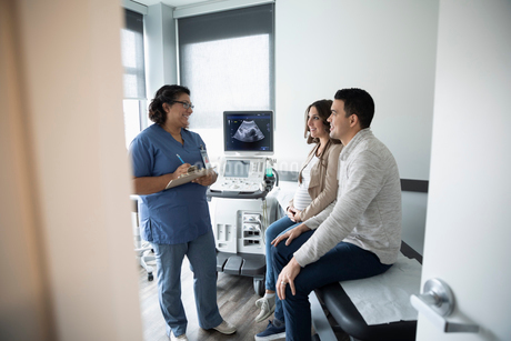 Female nurse talking with pregnant couple in clinic examination roomの写真素材 [FYI02334940]