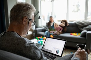 Senior man using laptop and drinking coffee in living roomの写真素材 [FYI02334944]