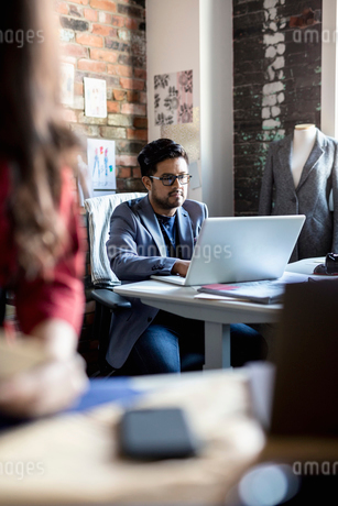 Focused male fashion designer working at laptop in officeの写真素材 [FYI02334947]