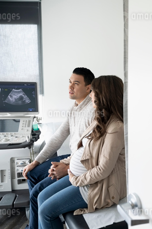 Pregnant couple holding hands after ultrasound in clinic examination roomの写真素材 [FYI02334970]