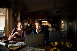 Couple paying bills at laptop in kitchenの写真素材 [FYI02334982]