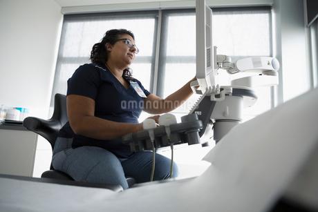 Female nurse using computer in clinic examination roomの写真素材 [FYI02334996]