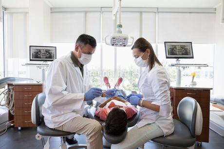 Dentist and dental hygienist checking teeth of boy in dentist officeの写真素材 [FYI02335002]