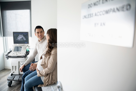 Pregnant couple waiting in clinic examination roomの写真素材 [FYI02335015]