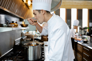 Chef tasting sauce at stove in restaurant kitchenの写真素材 [FYI02335038]