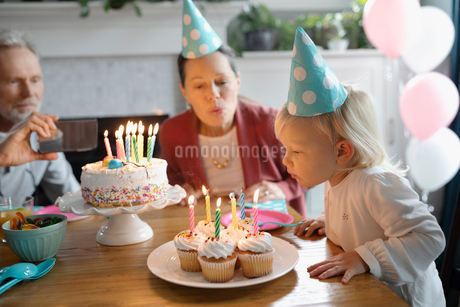 Grandparents and toddler granddaughter celebrating birthday, blowing out candlesの写真素材 [FYI02335065]