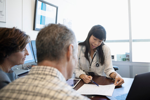 Female doctor showing test results to mature couple in doctor s officeの写真素材 [FYI02335075]