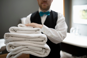 Male hotel staff with towels in hotel bathroomの写真素材 [FYI02335080]