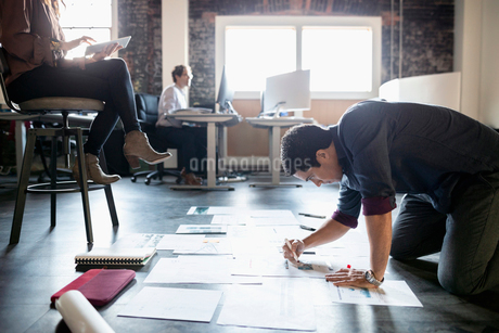 Dedicated creative businessman editing proofs on office floorの写真素材 [FYI02335178]