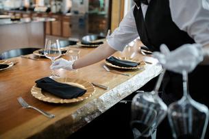 Female waitress in white gloves setting restaurant table with wine glassesの写真素材 [FYI02335208]