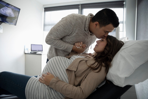 Affectionate, loving husband kissing forehead of pregnant wife in clinic examination roomの写真素材 [FYI02335230]