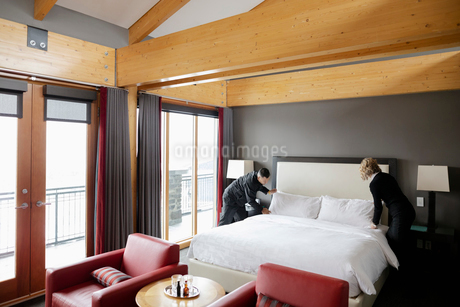 Hotel staff maids making bed in luxury hotel roomの写真素材 [FYI02335233]