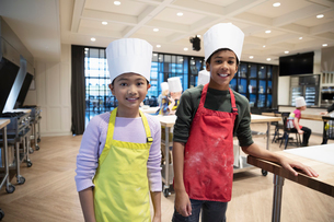 Portrait smiling, confident boy and girl in chefs hats enjoying cooking classの写真素材 [FYI02335331]