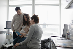 Female obstetrician talking with pregnant couple in clinic examination roomの写真素材 [FYI02335347]