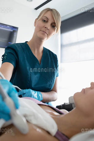 Female technician performing ultrasound soft tissue imaging on shoulder of patient in clinicの写真素材 [FYI02335387]