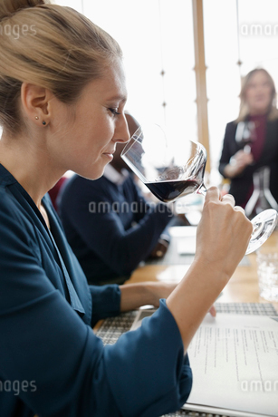Woman tasting red wine in restaurantの写真素材 [FYI02335394]