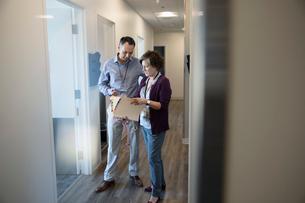 Doctors discussing medical record in clinic corridorの写真素材 [FYI02335416]