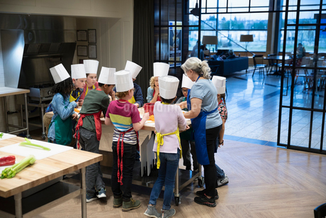 Woman leading childrens cooking classの写真素材 [FYI02335443]