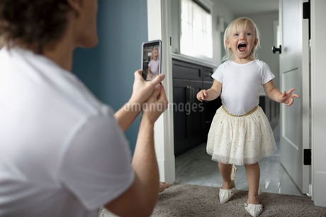 Father with camera phone photographing cute, playful toddler daughter in high heelsの写真素材 [FYI02335491]