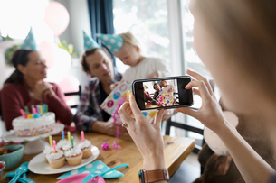 Woman with camera phone photographing toddler daughter opening birthday giftの写真素材 [FYI02335511]