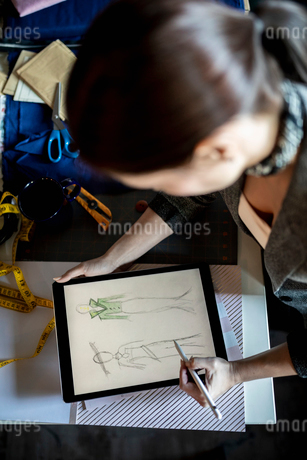 View from above female fashion designer sketching with digital tablet and stylusの写真素材 [FYI02335547]