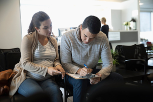Pregnant couple filling out paperwork in clinic waiting roomの写真素材 [FYI02335562]