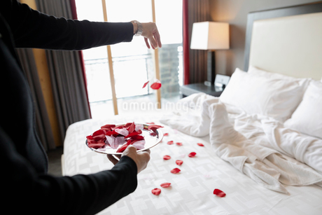 Female room service hotel staff sprinkling roses on luxury hotel room bedの写真素材 [FYI02335571]