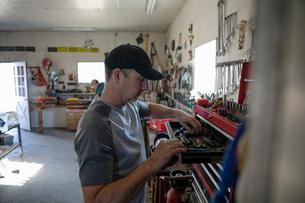 Man looking in toolbox in workshopの写真素材 [FYI02335602]