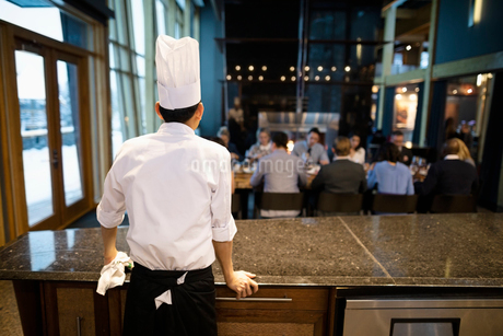 Executive chef watching people dining in restaurantの写真素材 [FYI02335636]