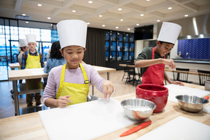 Children flouring surface in cooking classの写真素材 [FYI02335641]