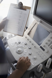 Technician with clipboard using ultrasound equipmentの写真素材 [FYI02335657]
