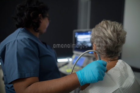 Female technician performing ultrasound soft tissue imaging on senior woman in clinic examination roの写真素材 [FYI02335666]