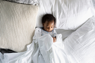 View from above innocent baby boy sleeping on bedの写真素材 [FYI02335686]