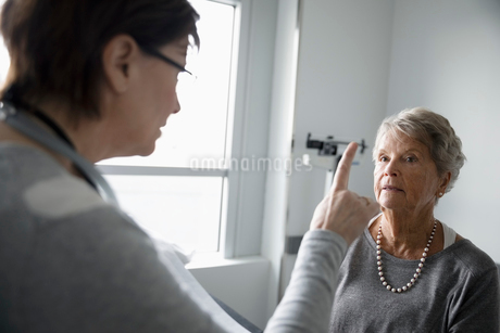 Female doctor checking vision of senior patient in clinic examination roomの写真素材 [FYI02335687]