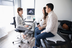 Female obstetrician talking with pregnant couple in clinic examination roomの写真素材 [FYI02335696]