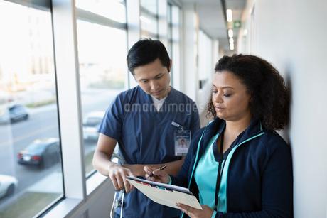 Nurses discussing medical record in clinic corridorの写真素材 [FYI02335702]