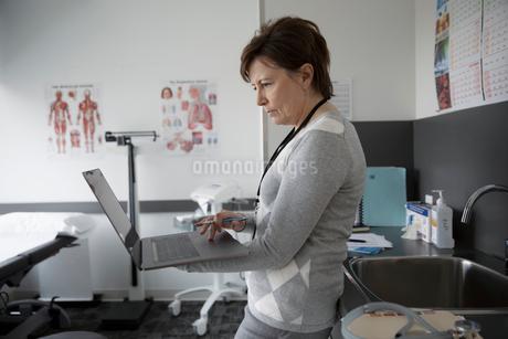Focused female doctor using laptop in clinic examination roomの写真素材 [FYI02335706]