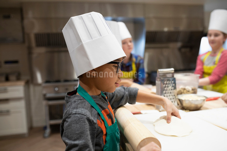 Boy rolling out pizza dough in cooking classの写真素材 [FYI02335708]