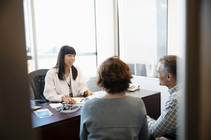 Female doctor talking with couple in doctor s officeの写真素材 [FYI02335767]