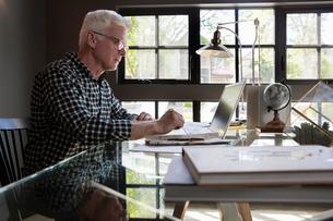 Senior man using laptop in home officeの写真素材 [FYI02335785]